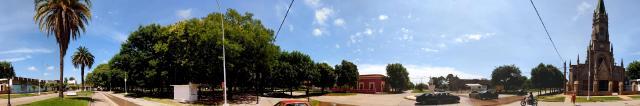 Centro y parroquia - imagen tomada en el cruce de las avenidas Mitre y Moreno, donde se aprecia la parroquia san Francisco Javier, el boulebard central, la plaza principal, el museo municipal y el monumento a Evita.